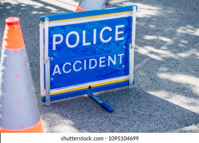 Surrey, UK. 5th May 2018. EDITORIAL - Elevated view of blue POLICE ACCIDENT sign beside two traffic cones, on a road in Surrey, UK.