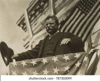 Surrounded by flags and bunting, Theodore Roosevelt looks out from a speakers platform. He was campaigning for a 3rd term as President in New Jersey, June or August, 1912