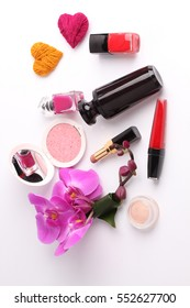 ?osmetics surrounded by flower on white background.