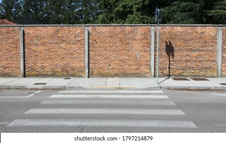 Surrounding brick wall, a concrete sidewalk, a crosswalk and a paved road ahead. Background for copy space