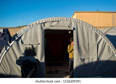 Suruc, Turkey - October 20, 2014. A Kurdish refugee boy from Kobani, stands inside his tent at a refugee camp in the Turkish town of Suruc, near the Turkish - Syrian border.