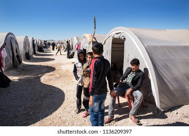 Suruc, Turkey - October 20, 2014. A Kurdish refugee boys from Kobani, sit outside their tent at a refugee camp in the Turkish town of Suruc, near the Turkish - Syrian border.