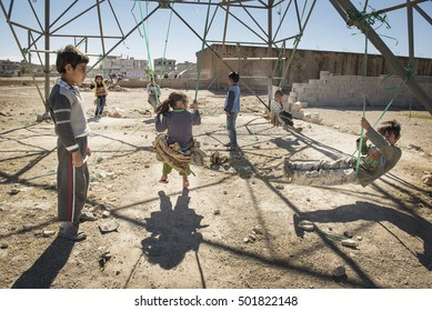Suruc, Turkey - October 20, 2014. Kurdish refugee children from Kobani, swing from an electricity power column, outside a refugee camp at the Turkish town of Suruc, near the Turkish - Syrian border.