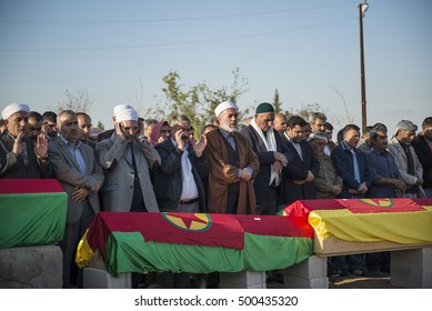 Suruc, Turkey - October 22, 2014. People pray during the funeral Kurdish fighters, killed while fighting Islamic State forces in Kobani, Syria, at the cemetery of Suruc, on the Turkey-Syria border.
