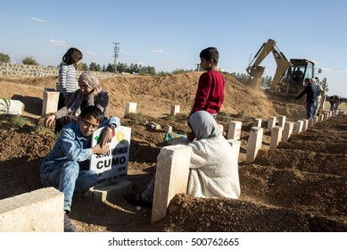 Suruc, Turkey - October 22, 2014. A Kurdish boy stands next the grave of his father, who was killed while fighting in Kobani against ISIS forces, at the cemetery of Suruc, at the Turkey-Syria border.