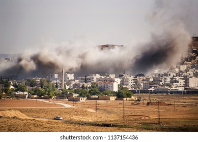 Suruc, Turkey - October 23, 2014. Smoke rises in Kobani, Syria, after an airstrike by the U.S.-led coalition, as seen from the top of a hill near Suruc, at the Turkish - Syrian border.