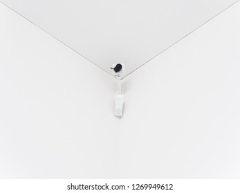 surveillance camera in a room corner with clean white background