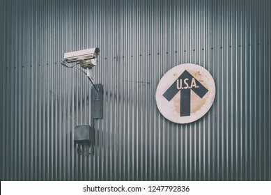 Surveillance camera with vintage USA direction sign on a steel wall