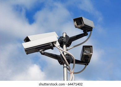 Surveillance cameras against blue sky