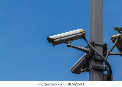 Surveillance cameras on a pole with a blue background.