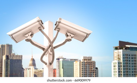 Surveillance CCTV camera and security concept - Dual surveillance cctv camera on pole in city tower with flare light effect and copyspace, Use for surveillance camera and security  content