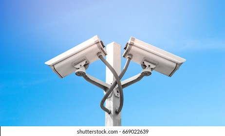 Surveillance CCTV camera and security concept - Dual surveillance cctv camera on pole with blue sky and flare light effect, Use for surveillance camera and security content