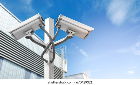 Surveillance CCTV camera and security concept - Dual surveillance cctv camera on pole in factory industrial with flare light effect and copyspace, Use for surveillance camera and security  content