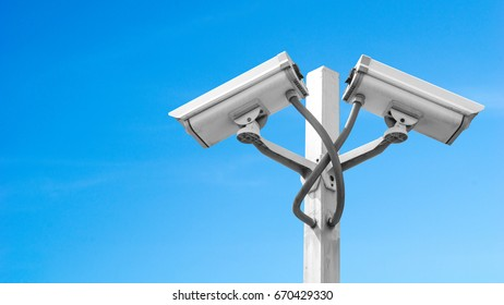 Surveillance CCTV camera and security concept - Dual surveillance cctv camera on pole with blue sky and copyspace, Use for surveillance camera and security content