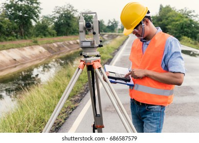 Survey by theodolite concept. Civil Engineer Checking Surveyor Equipment Tacheometer or theodolite outdoors at construction site on the road.