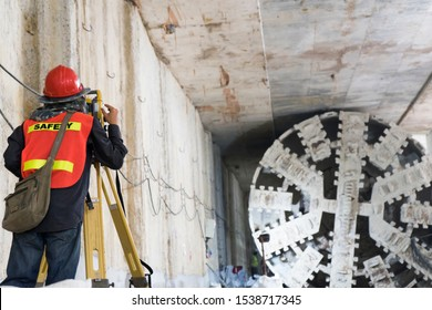 Survey staff wear a safety junction to look through a theodolite at the underground tunnel construction,Transport pipeline by Tunnel Boring Machine(TBM) method for electric train subway.