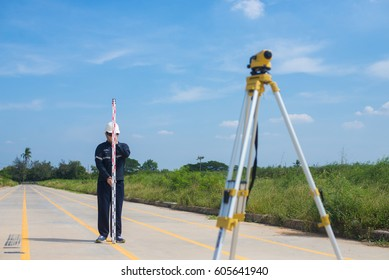 Surveying engineer is holding staff for checking to prepare the construction site by surveying equipment to check the leveling