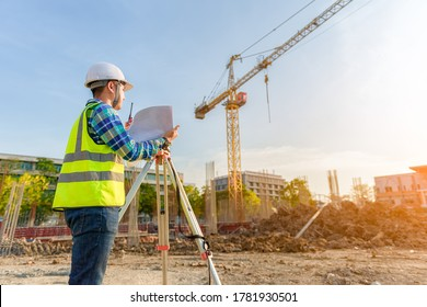 Surveying engineer working using theodolite on the construction site.