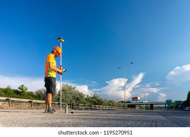 Surveyor engineer with GPS on construction site of the road during the sunny day