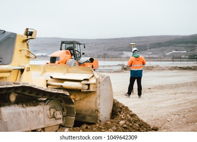 Surveyor engineer with GPS system outdoors at highway construction site, excavator and bulldozer details