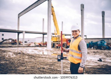 Surveyor engineer smiling with surveying tools and equipment at construction site outdoors, prefabricated cement pillars and beams