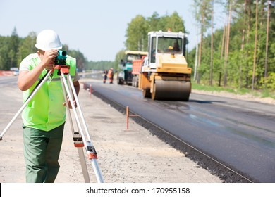 Surveyor engineer worker making measuring with theodolite instrument equipment during construction road works