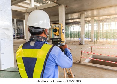 Surveyor engineer worker making measuring with theodolite equipment at construction site in new factory.