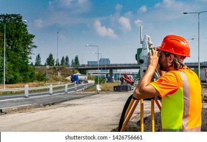 Surveyor engineer or worker with theodolite on construction site of road or highway during the sunny day with blue sky in background