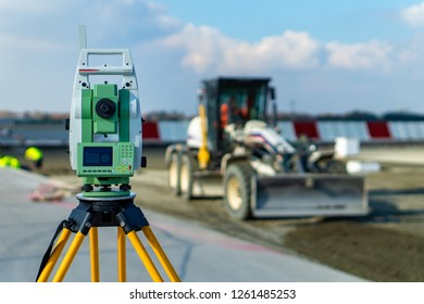 Surveyor equipment (theodolit) on construction site of the airport, building or road with construction machines in background