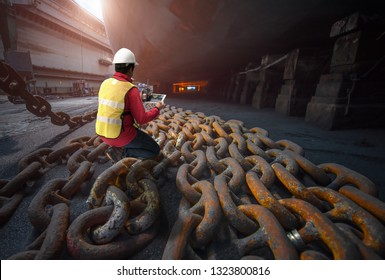 surveyor, inspector, port master inspect anchor chains bundle laying at bottom layer of the ship in floating dry dock terminal, for recondition maintennant with sand blasting perform