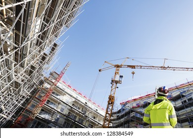 surveyor with instrument, surveying large building-site, super-.wide perspective