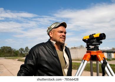 Surveyor measuring land for construction