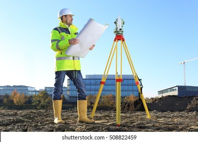 A Surveyor on a hill holding a Plan roll in hands