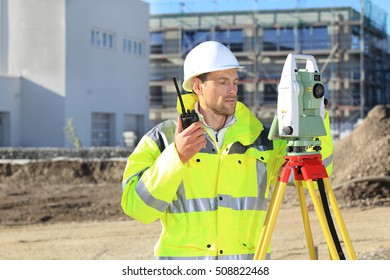 A Surveyor with surveying instrument and radio in front of a new buillding