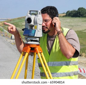 Surveyor with theodolite showing a direction