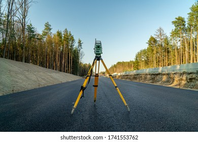 Surveyors equipment (theodolite or total positioning station) on the construction site of the road or building with construction machinery background
