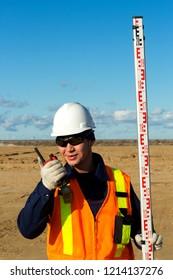 Surveyors leveling field site area. Professional surveyors working to level work area. Surveyor assistant helps to surveyor to level construction area. Surveyor uses survey equipment and radio.