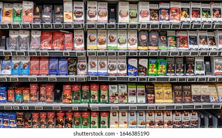 SURVILLIERS, FRANCE - FEBRUARY 14, 2020. In a hypermarket, shelves of bars of milk or dark chocolates of different brands and flavors.