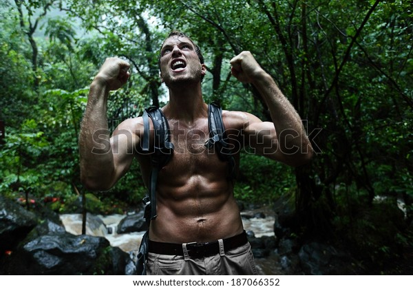 Survival man strong cheering in jungle rainforest. Muscular male survivor celebrating cheerful in forest at night showing muscles and aggressive survival instinct