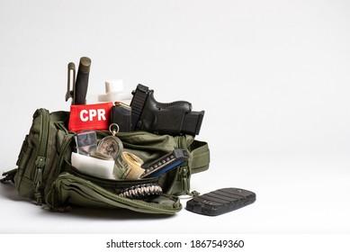 Kit de voyage de survie, petit sac bugout simple, clair, avec matériel médical, armes, GPS, boussole, dans un petit sac tactique vert olive isolé sur fond blanc avec place pour texte.