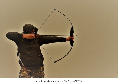 Survivalist shooting with bow and arrow