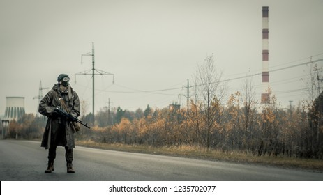 Survivor soldier in gas mask and with russian assault rifle walking in the danger radioactive zone of wastelands. Post apocalypse. Nuclear war.