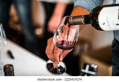 Susegana, Italy - October 2018: person pouring some red wine in a wine glass at a tasting section.