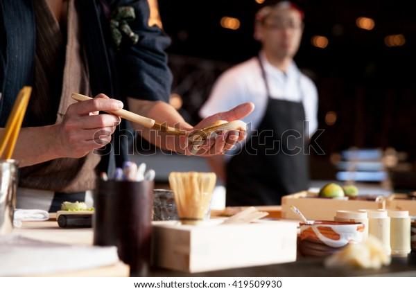 Sushi Chef making Nigiri. Omakase style Japanese fine dining.