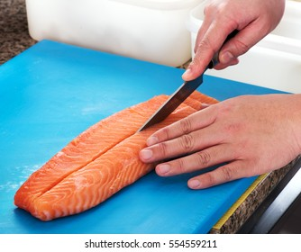 Sushi chef slicing a raw fresh salmon fillet with a sharp knife on a blue cutting board in a restaurant, close up of his hands