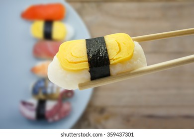 Sushi in chopsticks with sushi on a plate background