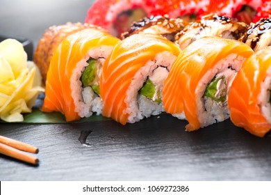 Sushi with chopsticks. Sushi roll japanese food in restaurant. California Sushi roll set with salmon, vegetables, flying fish roe and caviar closeup. Japan restaurant menu