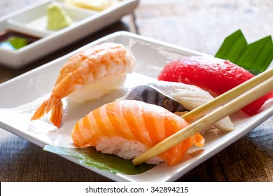 sushi with chopsticks.salmon,albacore,shrimp,tuna,and wasabi on the white plate on a wooden table.