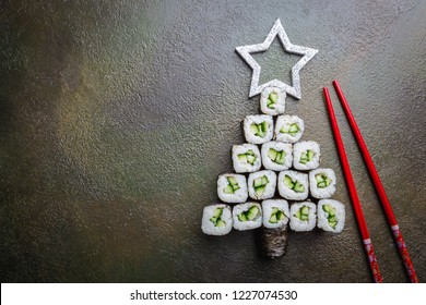 Sushi christmas tree with star over dark background, top view with copy space. Christmas or New Year background