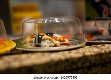 Sushi dish rides on a conveyor belt at a Japanese sushi bar.